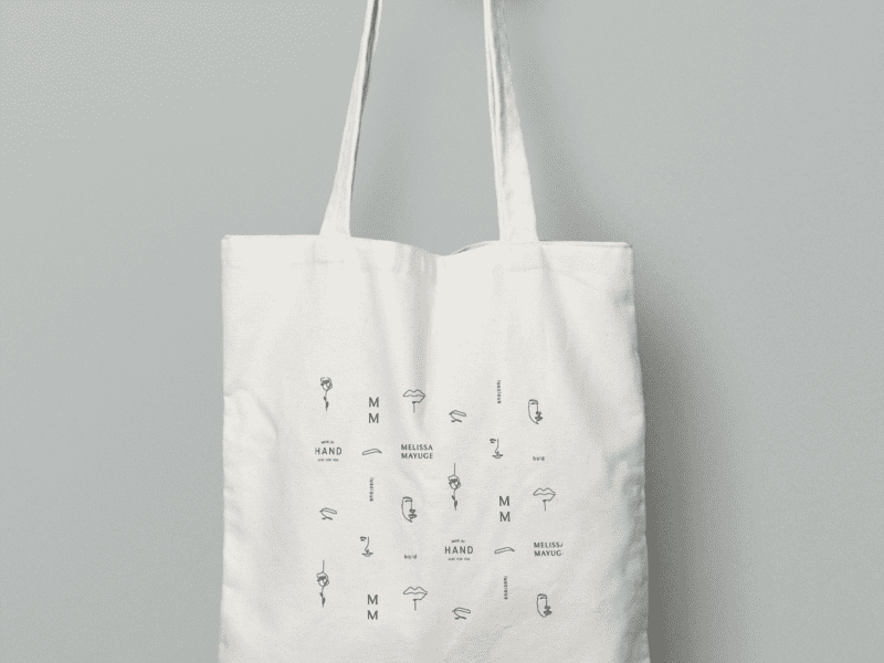 Hand holding canvas tote bag against wall