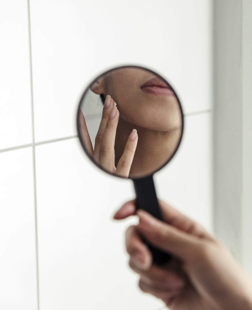 Woman touching face in small handheld mirror